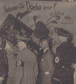 "Standing by the Dada wall at the ""Entartete Kunst"" (Degenerate Art) exhibition (1937)"